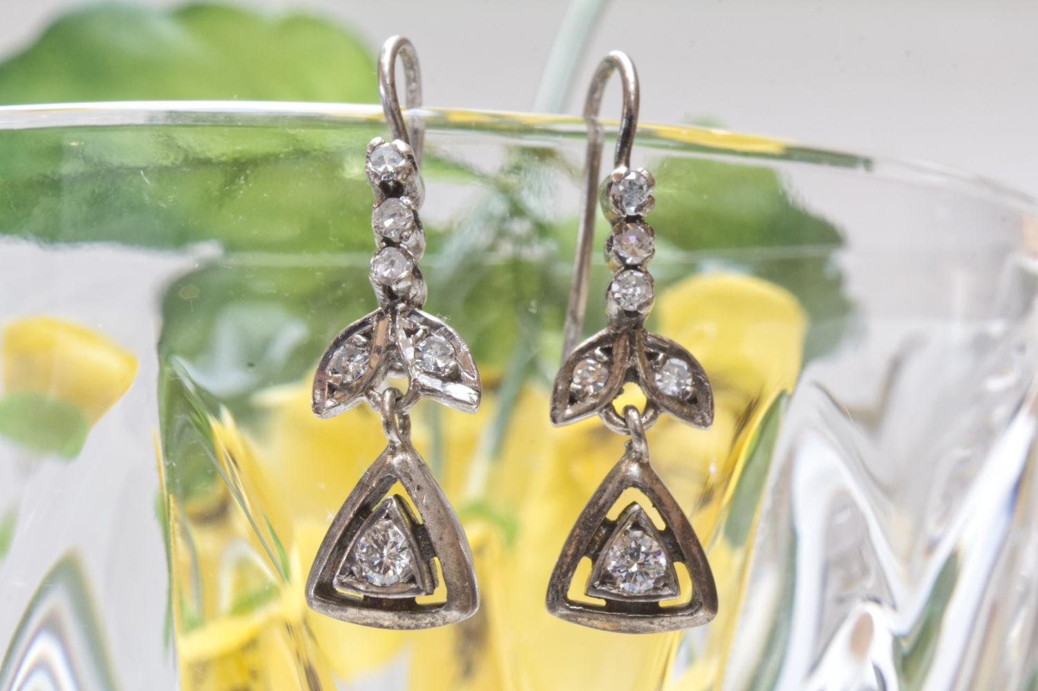 Antike Ohrringe aus Tombak mit Diamanten im Altschliff dekoriert auf Kristallglas.
