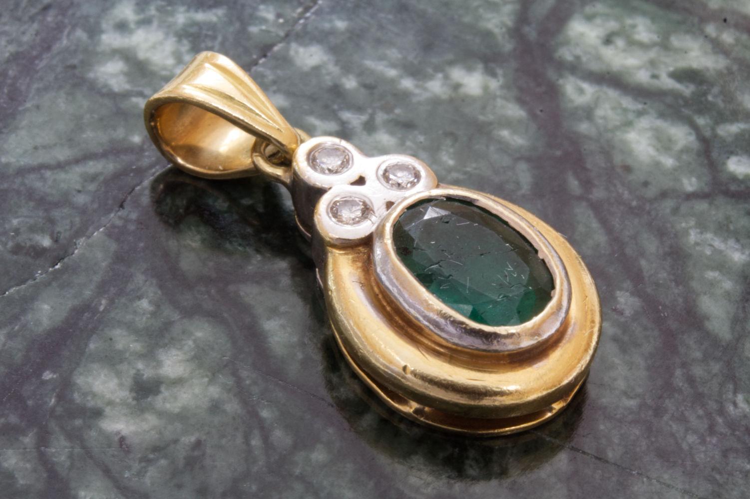 Anhänger mit Smaragd und Brllanten in 750er Gold gefasst und auf Marmor dekoriert.