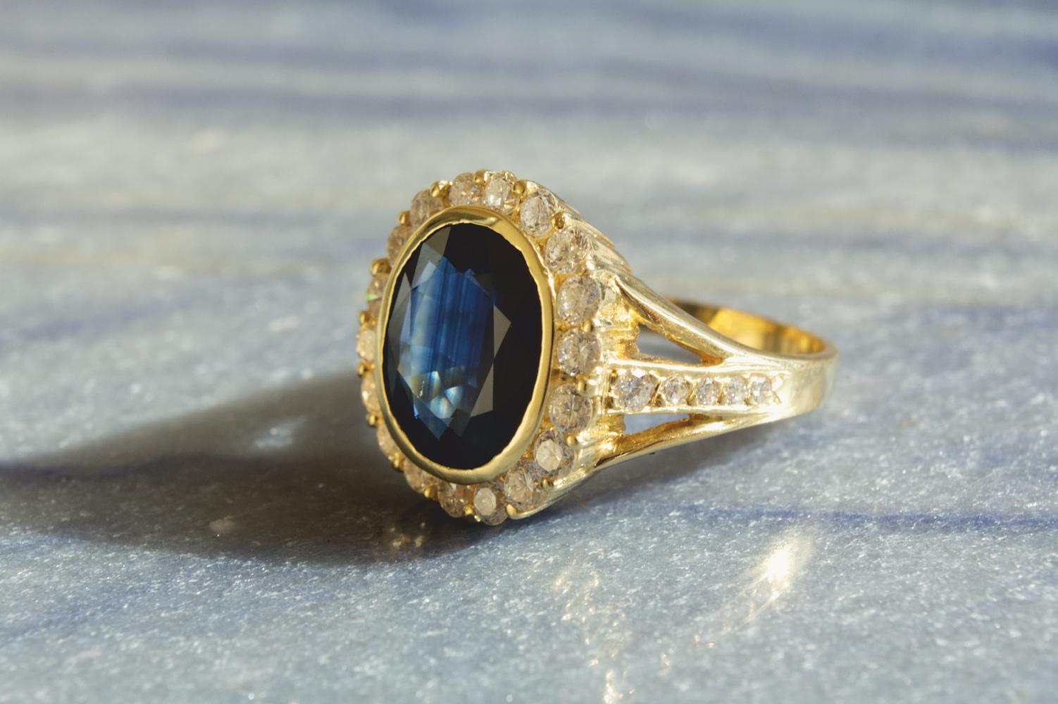 Eleganter Ring mit großem Saphir und Brillanten in Gelbgold in schöner Stimmung mit Softproof