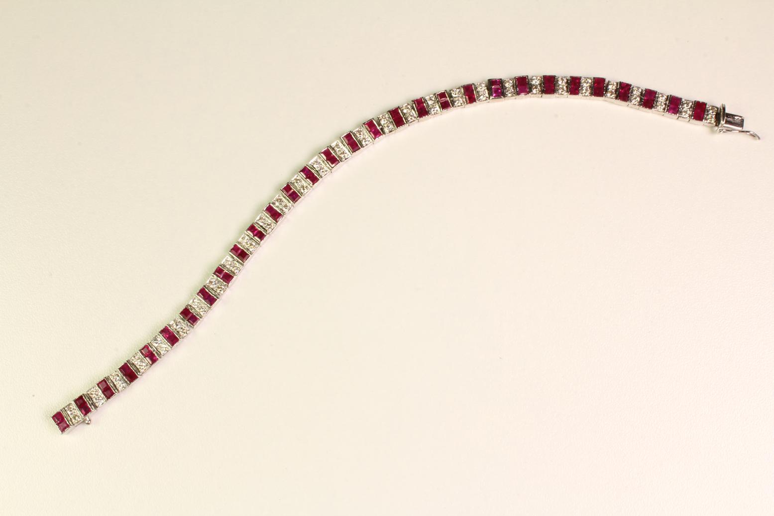 Antikes, französisches Armbandaus der Zeit des Art Deco. In 750er Weißgold gefasste Rubine, im Table Schliff, wechseln sich ab mit Diamanten im Altschliff und brillieren um die Wette. Ein exquisites Einzelstück für Sie! Rubine Diamanten 750 er Weißgold Lä