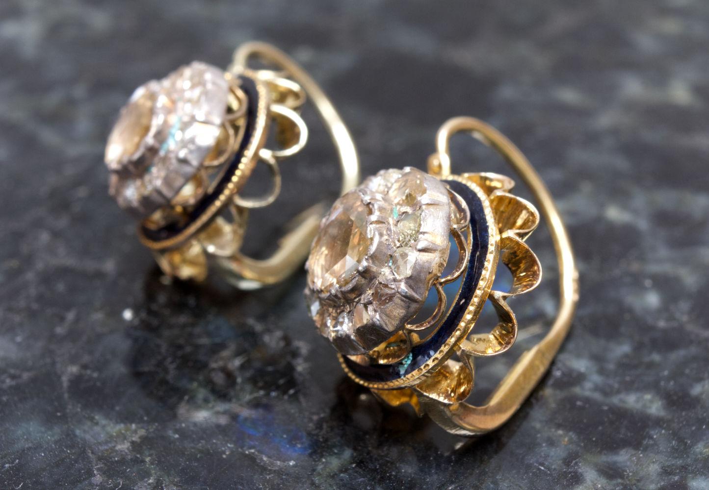 Ohrringe original antik mit Diamanten in Gold gefasst auf Marmor von der Seite gezeigt.