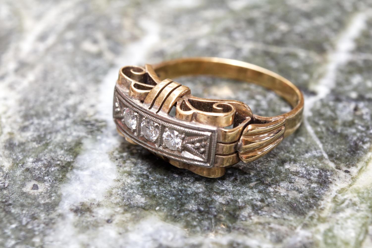 Antiker Ring mit Brillanten und in 585er Gold gefasst von der seitlichen Front auf Marmor zu sehen.